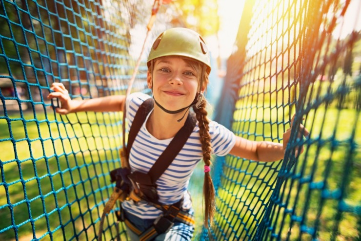 teenage-girl-having-fun-in-ropes-course-adventure-park-picture-id601137102