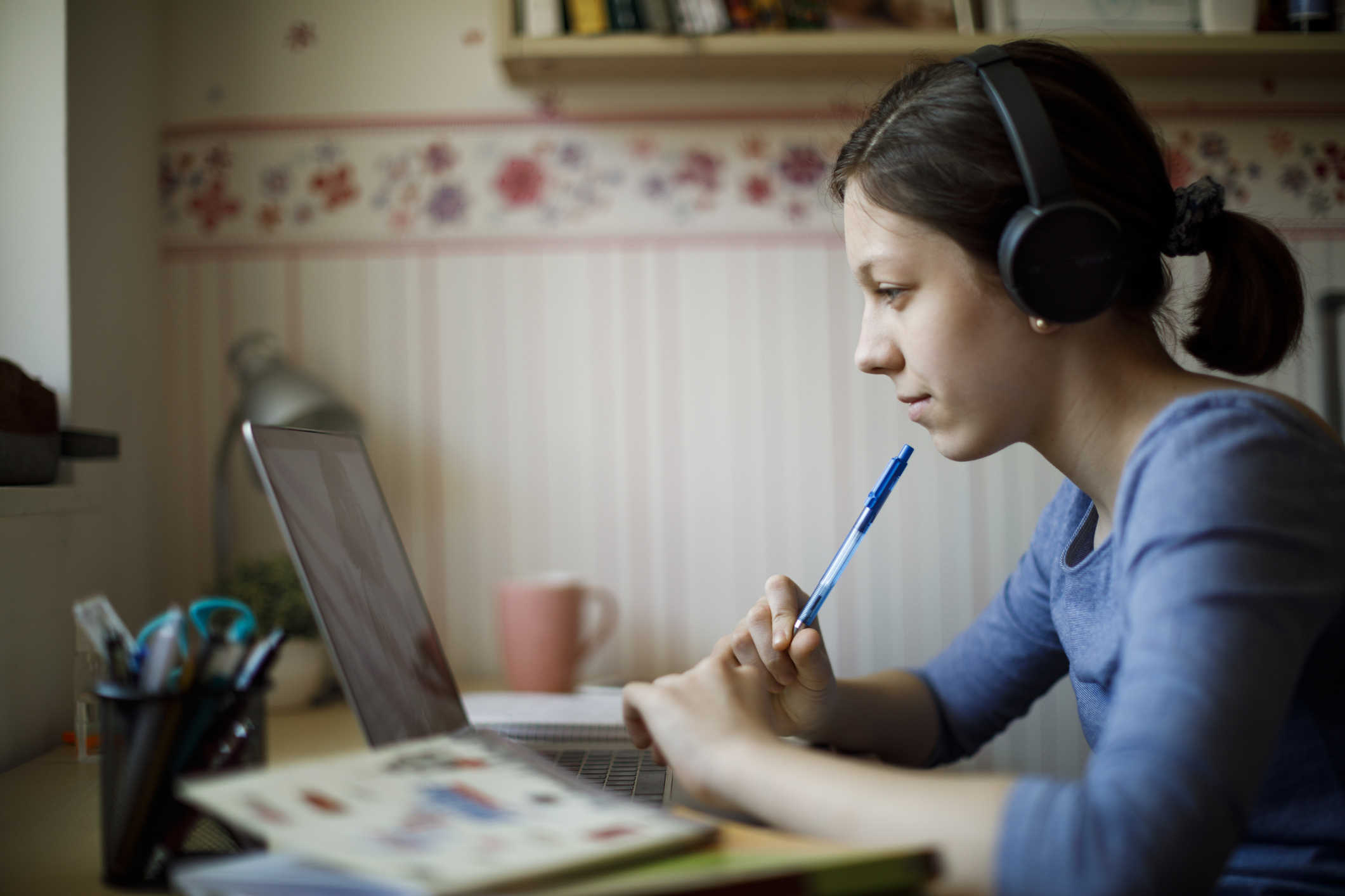 Teenage girl studying with video online lesson at home